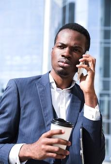 Portret młody biznesmen opowiada na telefonie komórkowym trzyma jednorazową filiżankę