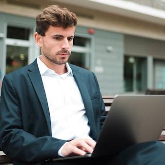 Portret młody biznesmen siedzi outdoors używać laptop