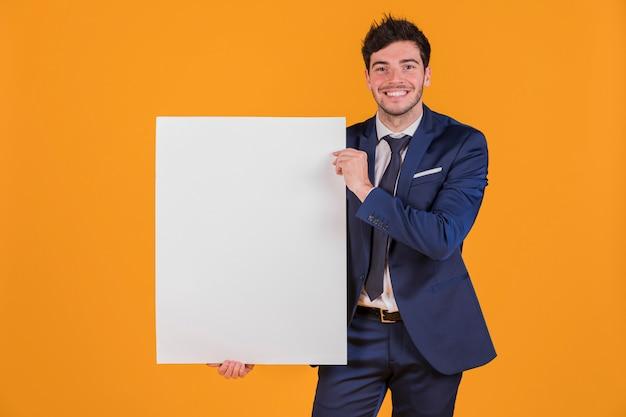 Portret młody biznesmen trzyma białego pustego plakat przeciw pomarańczowemu tłu