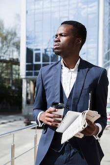 Portret młody biznesmen trzyma cyfrową pastylkę; gazeta i jednorazowa filiżanka kawy