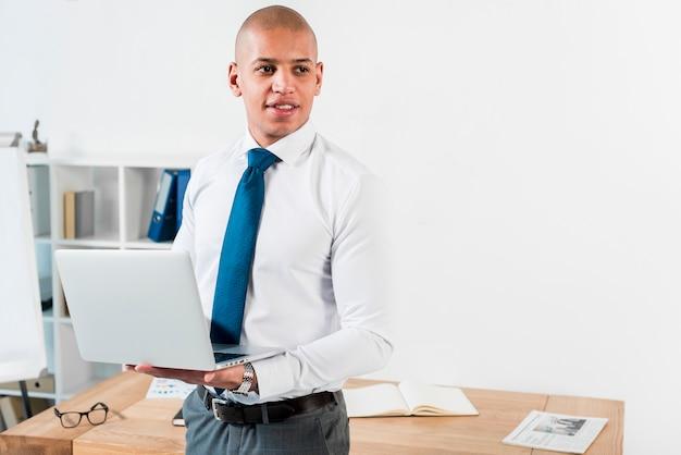 Portret młody biznesmen trzyma otwartego laptop w ręce patrzeje daleko od