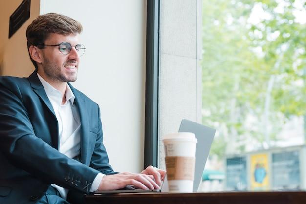 Portret młody biznesmen używa laptop z filiżanką na stole w kawiarni