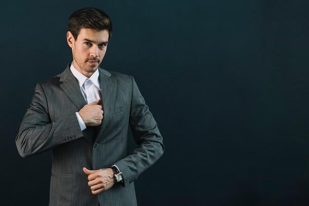 Portret młody biznesmen w kostium pozyci przeciw czarnemu tłu