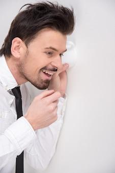 Portret młody biznesowy mężczyzna używa szkło jak telefon.