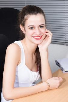 Portret młody bizneswoman siedzi w biurowego biurka ręce pod podbródkiem
