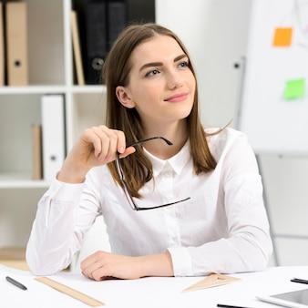 Portret młody bizneswoman z eyeglass w ręki główkowaniu