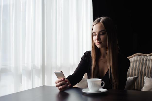 Portret młody bizneswomanu use telefon komórkowy podczas gdy siedzący w wygodnym sklep z kawą podczas pracy przerwy.