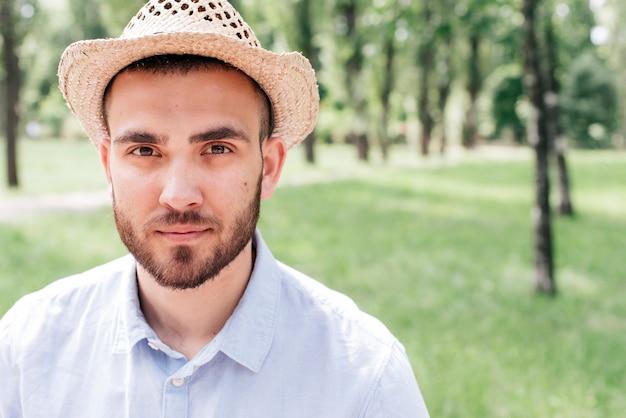 Portret młody brodaty mężczyzna jest ubranym kapelusz przy parkiem