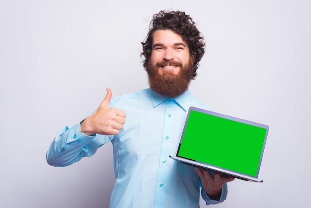 Portret młody brodaty mężczyzna w dorywczo pokazując kciuk w górę gest i trzymając laptop z zielonym ekranem