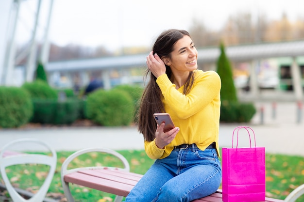 Portret młody brunetki kobiety siedzieć plenerowy na ławce z torba na zakupy i używać telefon komórkowego. kobieta ubrana w żółty sweter