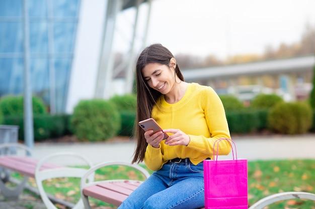 Portret młody brunetki kobiety siedzieć plenerowy na ławce z torba na zakupy i używać telefon komórkowego.