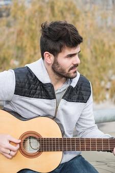 Portret młody człowiek bawić się gitarę przy outdoors