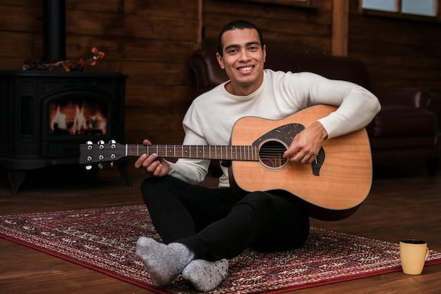 Portret młody człowiek bawić się gitarę