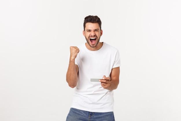 Portret młody człowiek bawić się wideo gry na telefonie komórkowym na szarość.