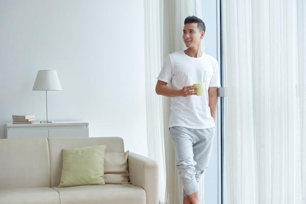 Portret młody człowiek cieszy się ranek przy hiome z filiżanką herbaciana pozycja przy niecki okno