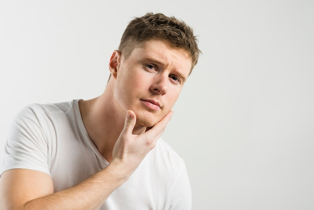 Portret młody człowiek dotyka jego twarz przeciw białemu tłu