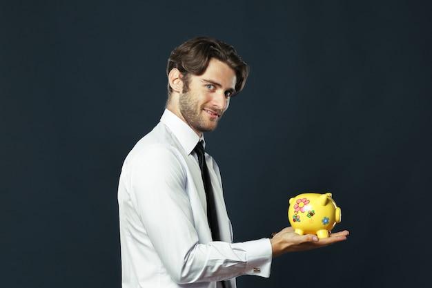Portret młody człowiek i trzymać prosiątko banka