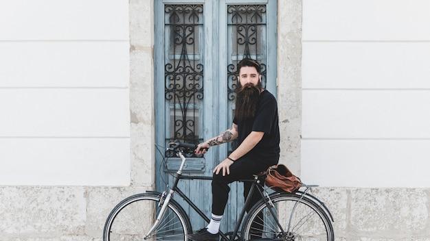 Portret młody człowiek jedzie bicykl przeciw zamkniętemu drzwi