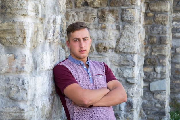 Portret młody człowiek na kamiennej ściany tle
