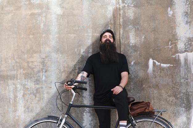 Portret młody człowiek opiera na ścianie z bicyklem
