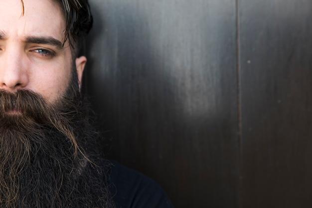 Portret młody człowiek patrzeje kamerę z długą brodą
