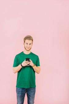 Portret młody człowiek patrzeje kamerę z telefonem komórkowym