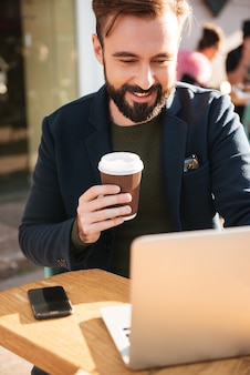 Portret młody człowiek pracuje na laptopie