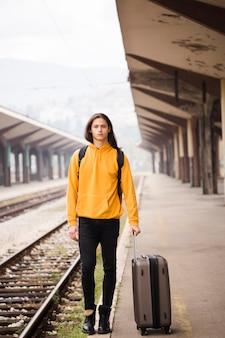 Portret młody człowiek przy stacją kolejową