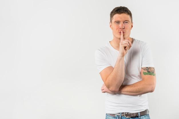 Portret młody człowiek robi gestykulować dla ciszy z palcem