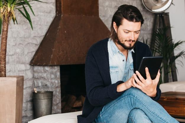 Portret młody człowiek siedzi w domu wyszukuje jego telefon komórkowego