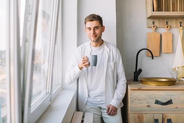 Portret młody człowiek trzyma filiżanki kawy pozycję w kuchni