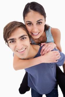 Portret młody człowiek trzyma jego dziewczyny na jego z powrotem