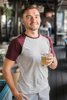 Portret młody człowiek trzyma szkło piwo