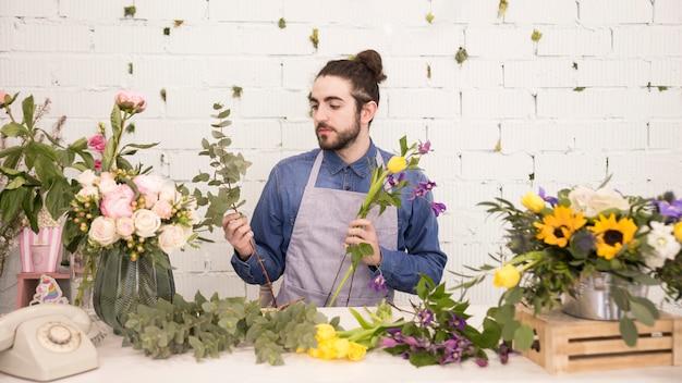 Portret młody człowiek tworzy kwiatu bukiet w kwiatu sklepie