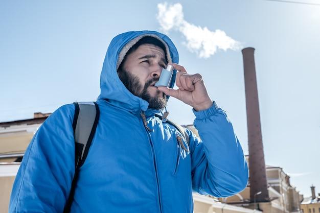 Portret młody człowiek używa astma inhalator plenerowego