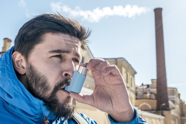 Portret młody człowiek używa astma inhalator