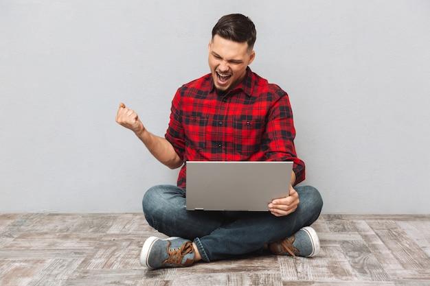 Portret młody człowiek używa laptop i świętuje sukces