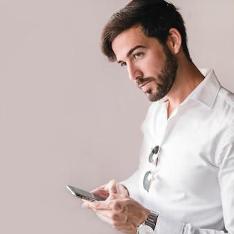 Portret młody człowiek używa smartphone