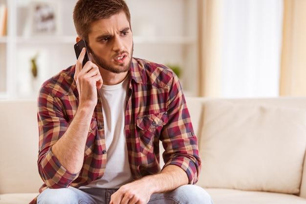 Portret młody człowiek używa telefon w domu.