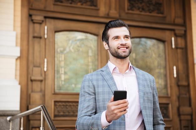 Portret młody człowiek w kurtce używać telefon komórkowego