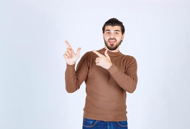 Portret młody człowiek wskazuje palce up przy kopii przestrzenią odizolowywającą nad białym tłem. zdjęcie wysokiej jakości