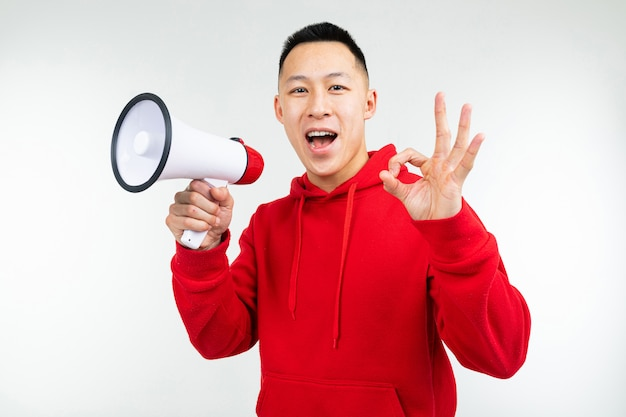 Portret młody człowiek z głośnikiem w jego rękach na białym pracownianym tle