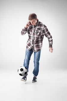 Portret młody człowiek z mądrze telefonem i futbolową piłką