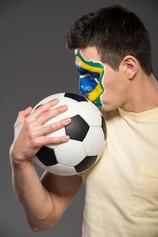 Portret młody człowiek z piłki nożnej piłką i brazylijską flaga.
