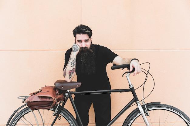 Portret młody człowiek z tatuażem na jego ręki pozyci z bicyklem przeciw ścianie