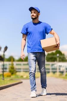 Portret młody doręczeniowego mężczyzna przewożenia pudełko