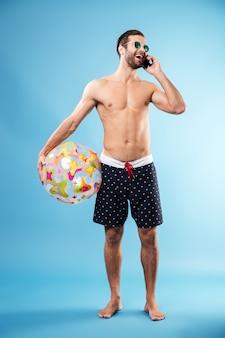 Portret młody facet trzyma plażową piłkę