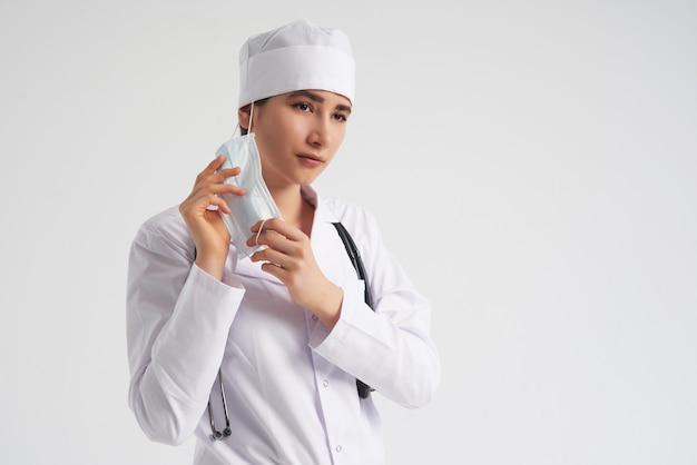 Portret młody kobiety lekarki kładzenie na ochronnej medycznej twarzy masce na biel ścianie, kopii przestrzeń