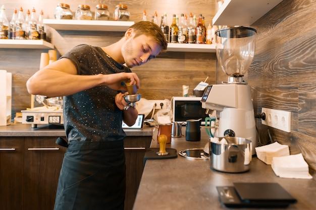Portret młody męski barista robi napojom. biznes kawowy