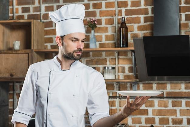 Portret młody męski profesjonalisty kucharz trzyma pustego bielu talerza w ręce